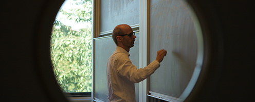 Male professor writing on a blackboard